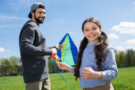 smiling child with father holding kite on meadow