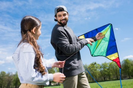 father and daughter holding kite on meadow in park