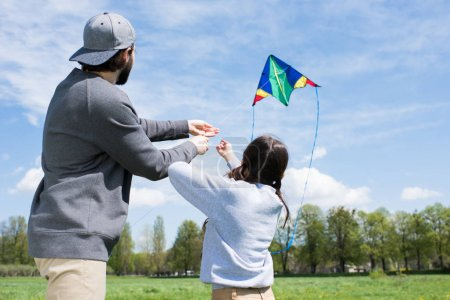 rear view of father and daughter flying kite on meadow