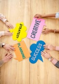 overhead view of multiracial business people at wooden table with colorful chat bubbles with strategy, planning, creative, success signs