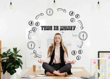 calm businesswoman meditating in lotus position on table in office with time for money inscription and money and time circuit