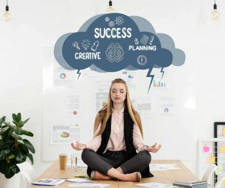 calm businesswoman meditating in lotus position on table in office, cloud with creative success planning signs inside above head