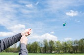 cropped image of man flying kite on meadow in park
