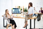 selective focus of multiethnic businesswomen at workplace with financial protection inscription on screen and colleagues behind in office