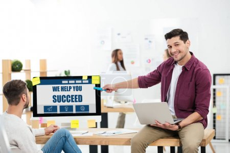 businessman pointing at we help you succeed inscription on computer screen while working at workplace with colleague in office