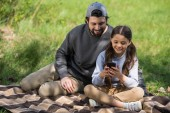 smiling father watching daughter using smartphone on plaid in park