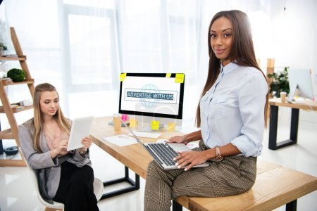 young multicultural businesswomen working in office with advertise with us inscription on computer screen