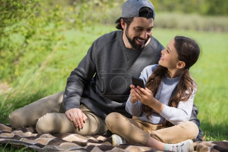 father watching daughter using smartphone on plaid in park