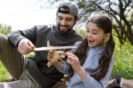 smiling daughter and father playing with wooden airplane in park