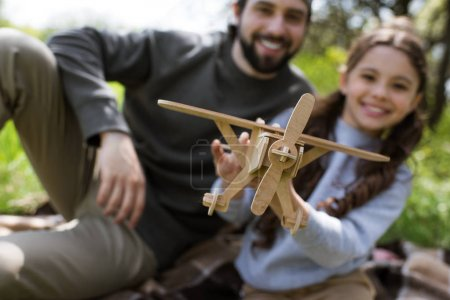 closeup view of wooden toy plane in hands of girl sitting on plaid with father in park