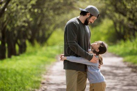 Photo pour Vue latérale de sourire fille étreignant père dans le parc - image libre de droit