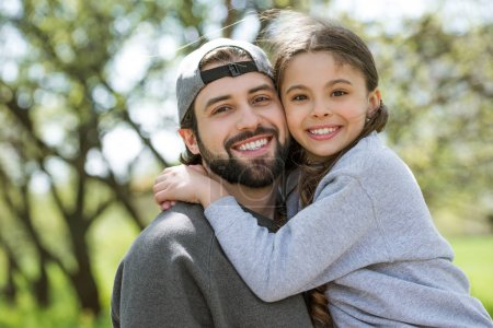 happy daughter embracing father in park
