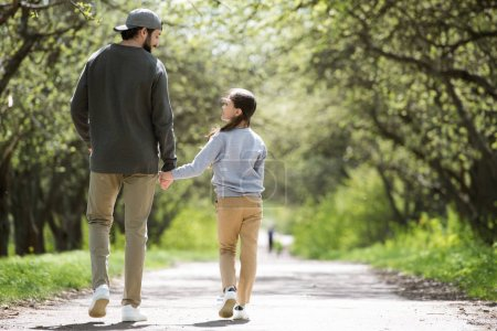 Photo pour Vue arrière du père et de la fille marchant et se tenant la main dans le parc - image libre de droit