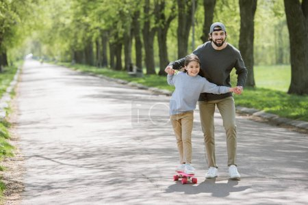 smiling father holding daughter hands while she riding on skateboard in park