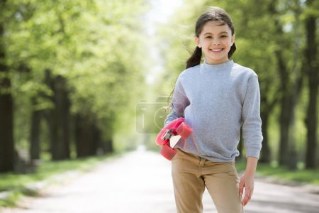 little smiling child holding penny board in park
