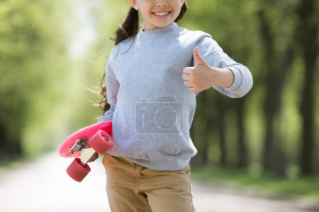 cropped image of child with penny board doing thumb up gesture
