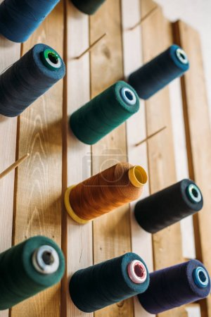 colored thread coils hanging on wooden surface at sewing workshop
