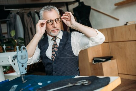 senior tailor wearing glasses for sewing at sewing workshop
