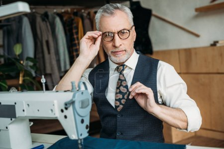 senior tailor touching glasses and looking at camera at sewing workshop