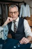 handsome senior tailor looking at camera at sewing workshop