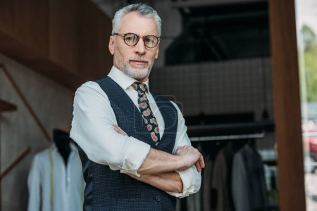 Photo pour Beau tailleur senior debout avec les bras croisés et regardant la caméra à l'atelier de couture - image libre de droit
