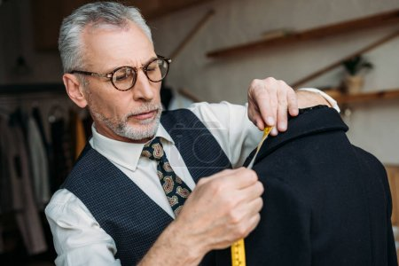 handsome senior tailor measuring jacket with tape measure at sewing workshop