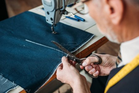 cropped image of senior tailor cutting cloth at sewing workshop
