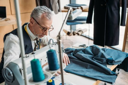 handsome tailor sewing blue cloth with sewing machine at sewing workshop