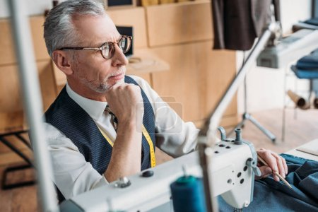 pensive tailor sitting at table with sewing machine and looking away at sewing workshop