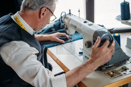 side view of tailor sewing cloth with sewing machine at sewing workshop
