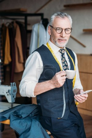 handsome tailor standing with cup of coffee and smartphone at sewing workshop