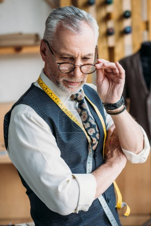 handsome tailor touching glasses and looking down at sewing workshop