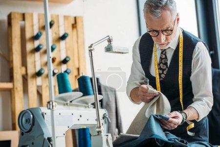 Photo pour Beau tailleur au choix entre des vêtements sombres et clairs à l'atelier de couture - image libre de droit