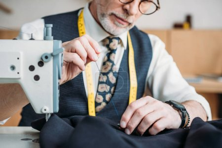 cropped image of senior tailor sewing button to jacket at sewing workshop