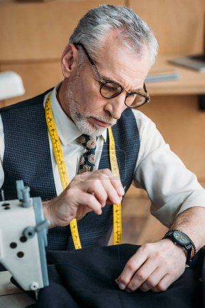 handsome tailor sewing button to jacket at sewing workshop