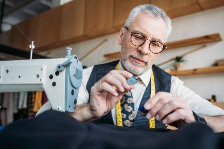 handsome tailor holding buttons at sewing workshop