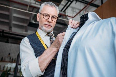 Photo pour Vue à angle bas du beau tailleur mesurant chemise à l'atelier de couture - image libre de droit