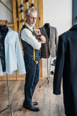 handsome grey hair tailor looking at jackets on mannequins at sewing workshop