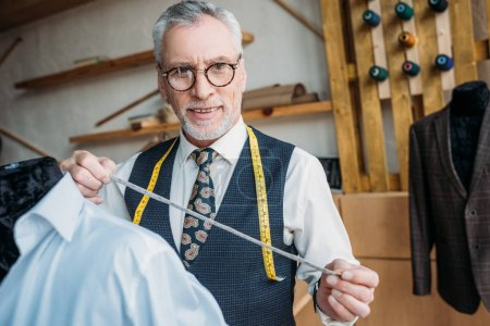 handsome tailor measuring jacket with tape measure at sewing workshop