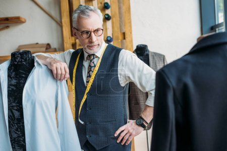 Photo for Handsome tailor leaning on mannequin at sewing workshop and looking at jacket - Royalty Free Image