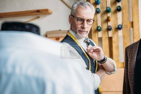 handsome senior tailor looking at jackets on mannequins at sewing workshop