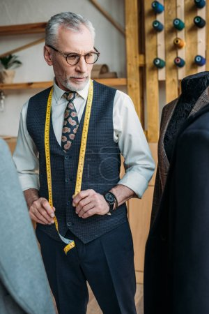 handsome tailor looking at jackets on mannequins at sewing workshop