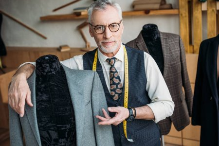 Photo for Handsome tailor showing jacket on mannequin at sewing workshop - Royalty Free Image