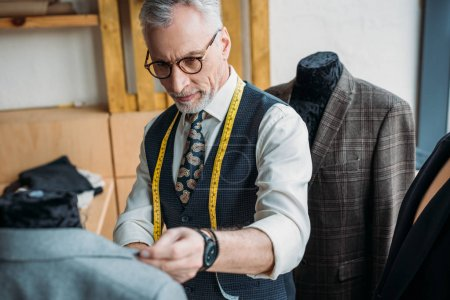 handsome mature tailor with measuring tape looking at jacket on mannequin at sewing workshop