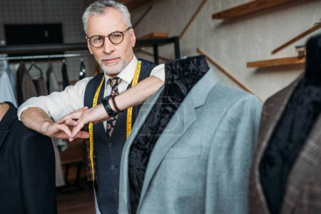 stylish mature tailor with measuring tape leaning on mannequin with jacket at sewing workshop