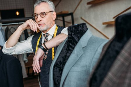 thoughtful mature tailor with measuring tape leaning on mannequin with jacket at sewing workshop