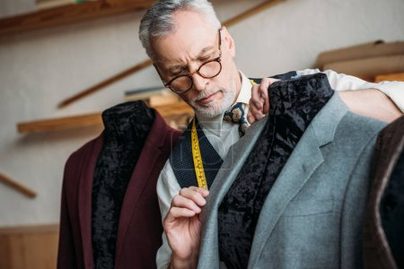 concentrated mature tailor with measuring tape examining jacket on mannequin at sewing workshop