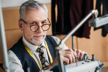 stylish mature tailor working with sewing machine at workshop and looking at camera