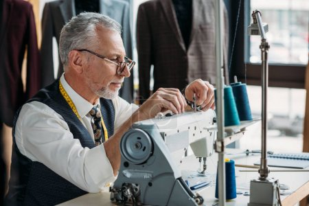 confident mature tailor working with modern sewing machine at workshop