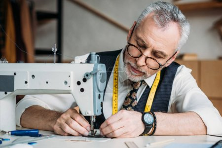 focused mature tailor working with sewing machine at workshop